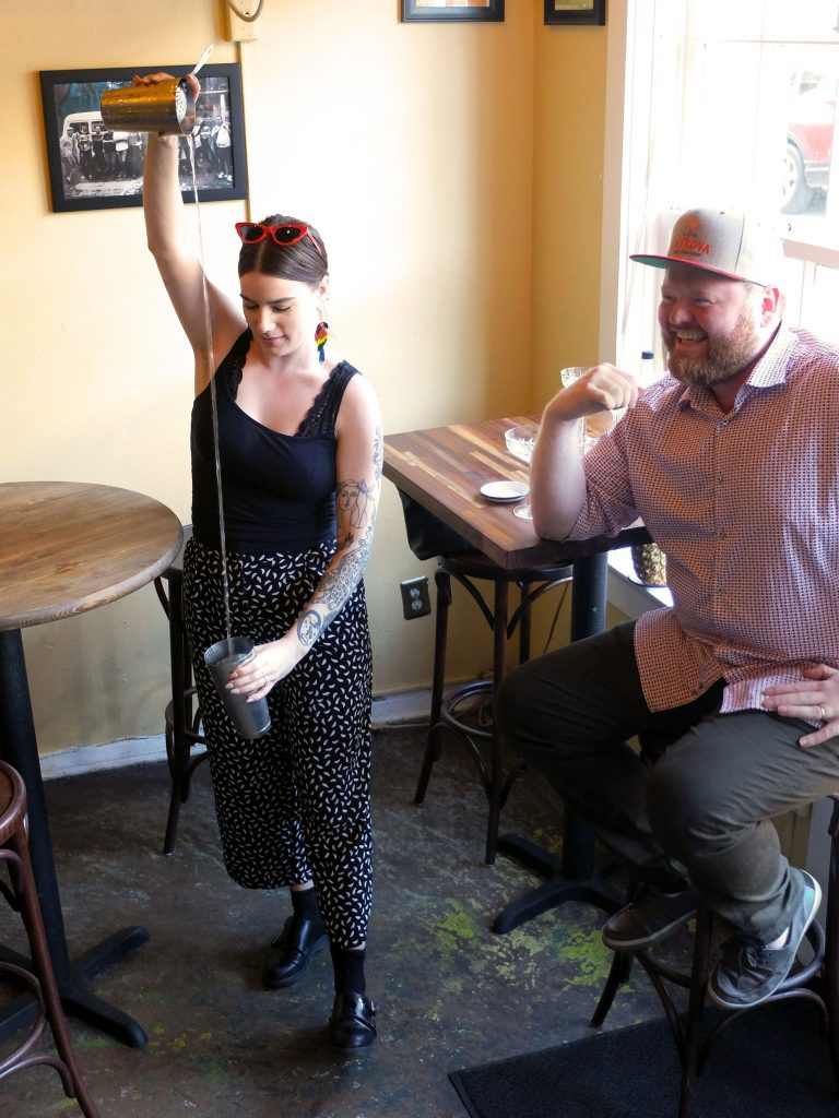 A thrown cocktail demonstrated by Maggie Morgan as Nick Detrich looks on.