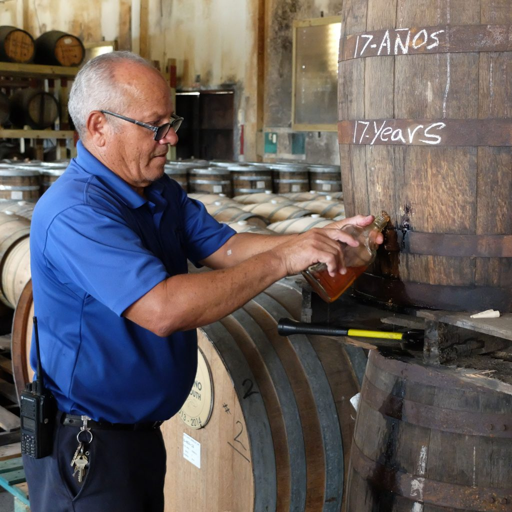 Noel García, who has worked in the cooperage at Destilería Serrallés for thirty-two years, samples some seventeen year old. Photo by Ben Schaffer.